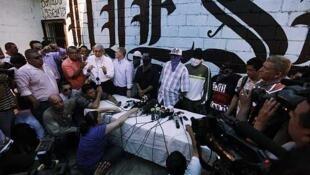 """El obispo de San Pedro Sula,  Rómulo Emiliani, habla con la prensa junto a miembros de la pandilla """"Calle 18"""", el 28 de mayo de 2013."""