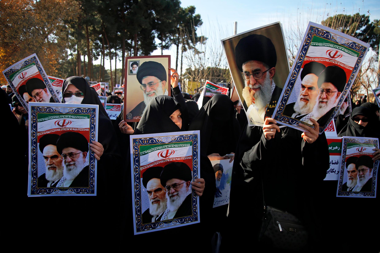 Des partisans du régime iranien brandissent des affiches à l'effigie du président Hassan Rohani et du Guide suprême Ali Khamenei, le 3 janvier 2018 à Qom, au sud de Téhéran.