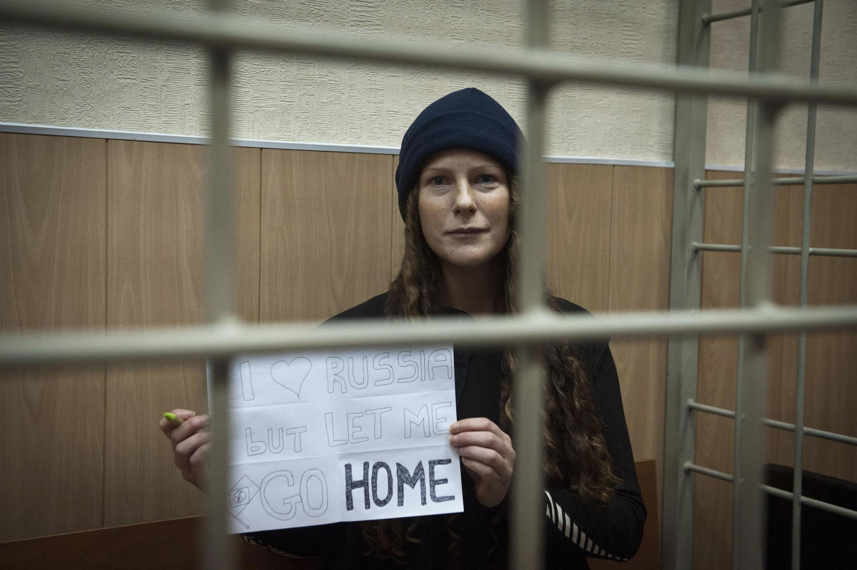 A bióloga brasileira Ana Paula Maciel exibe cartaz pedindo para voltar para casa.