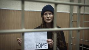 A bióloga brasileira Ana Paula Maciel exibe cartaz pedindo para voltar para casa; a justiça russa determinou nesta terça-feira, 19 de novembro de 2013, sua libertação sob fiança.