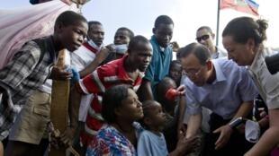 Le secrétaire général de l'ONU Ban Ki-moon (2e d) avec des déplacés haïtiens à Port-au-Prince, le 17 janvier 2010.