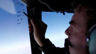 Brett McKenzie, le chef de l'escadron de recherche de l'épave de l'avion du vol MH370, prend des notes.