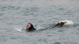 Muçulmana toma banho de mar coberta em Marselha, no sul da França.