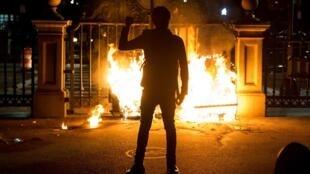 Un manifestant, poing levé, devant la porte en flammes du Boston Public Garden, le 31 mai 2020.