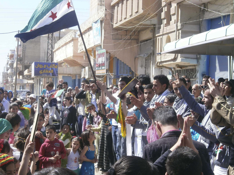 Des Syriens brandissant le drapeau de l'indépendance. Durant 2012, plusieurs manifestations ont eu lieu contre le régime répressif de Bachar el-Assad.
