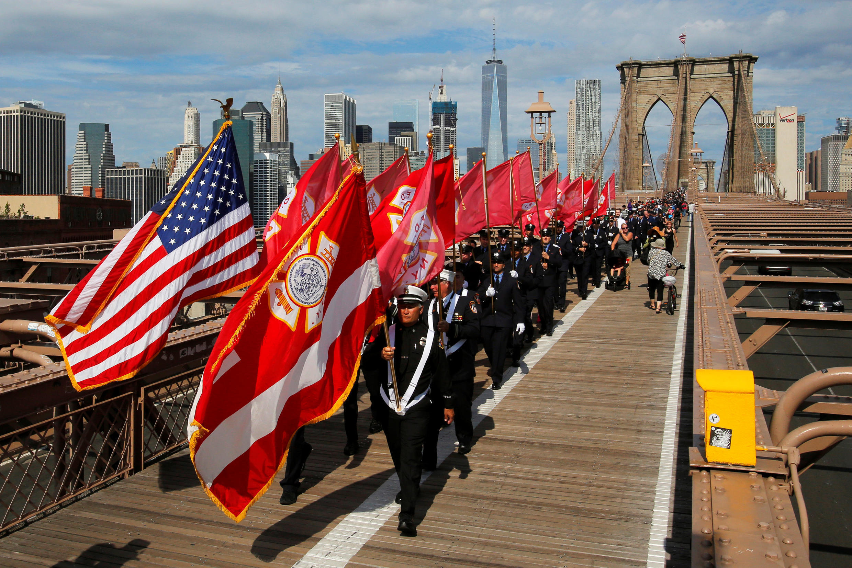 Des pompiers new-yorkais défilent ce 11 septembre 2016 au-dessus du Brooklyn Bridge, en mémoire de leurs collègues tombés lors des attaques du 11 septembre 2001.