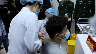 Vietnamese military medical officials administer a shot of the Covid-19 vaccine Nanocovax to a volunteer in Hanoi