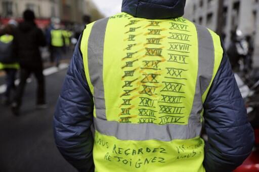 Un manifestante con la lista de los 'Actos' de protesta en su chaleco amarillo, Par!s, 13 de abril.
