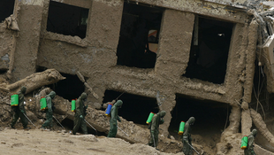 Des secouristes désinfectent une rue touchée par un glissement de terrain, à Zhougu, dans la province de Gansu, le 11 août 2010.