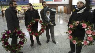 Membros da milícia iraniana El Bassidj aguardam diplomatas iranianos no aeroporto