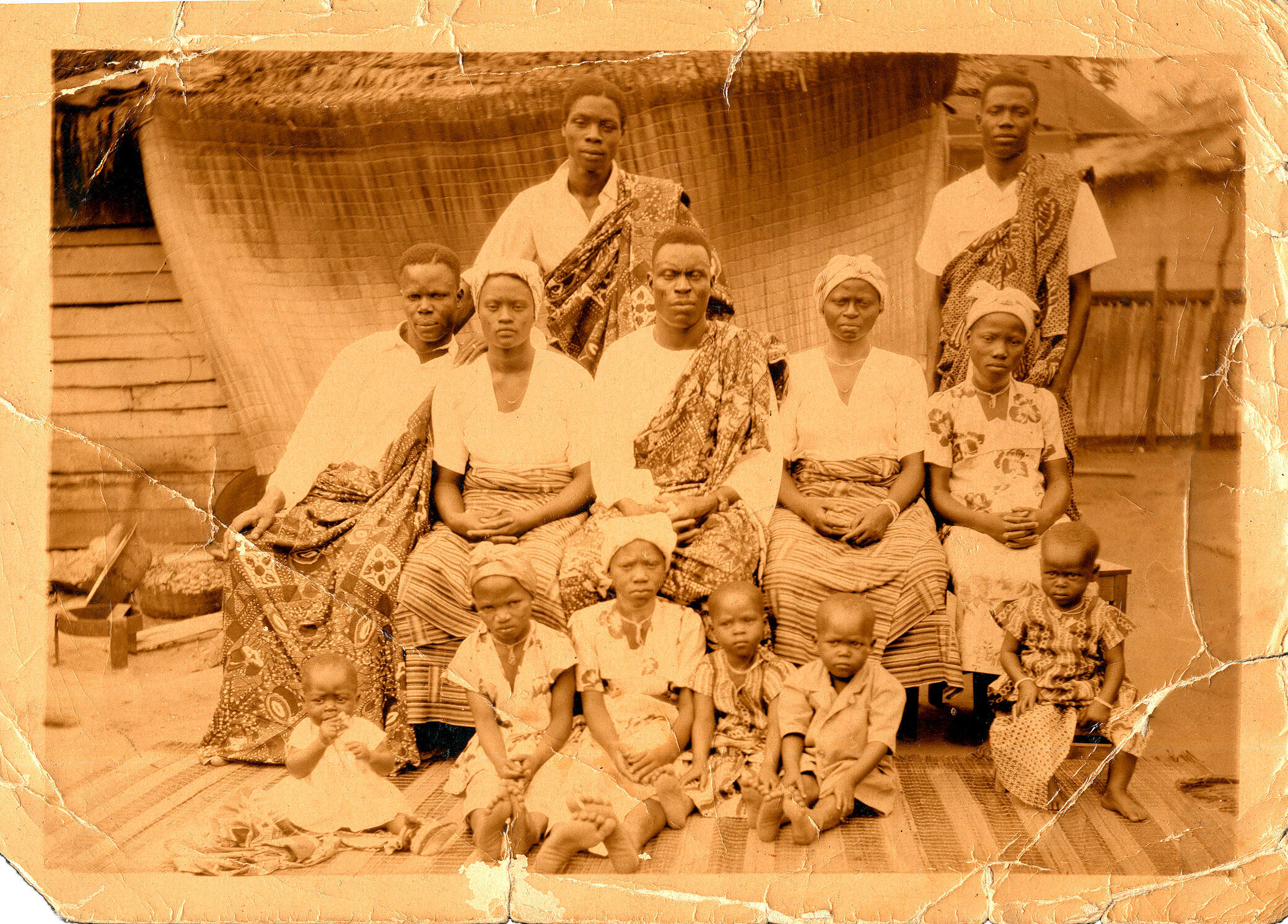 Beninese men (standing up) have their photograph taken with family before leaving for France circa 1950