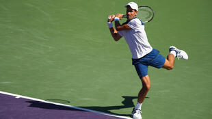 Novak Djokovic of Serbia in action against Benoit Paire of France in their second round match during the Miami Open on March 23, 2018.