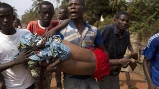 Des hommes transportent un blessé, décédé par la suite de ses blessures.