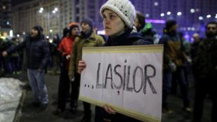 Une manifestante porte une pancarte où inscrit le mot «lâches» lors d'un rassemblement à Bucarest, le 31 janvier 2017.