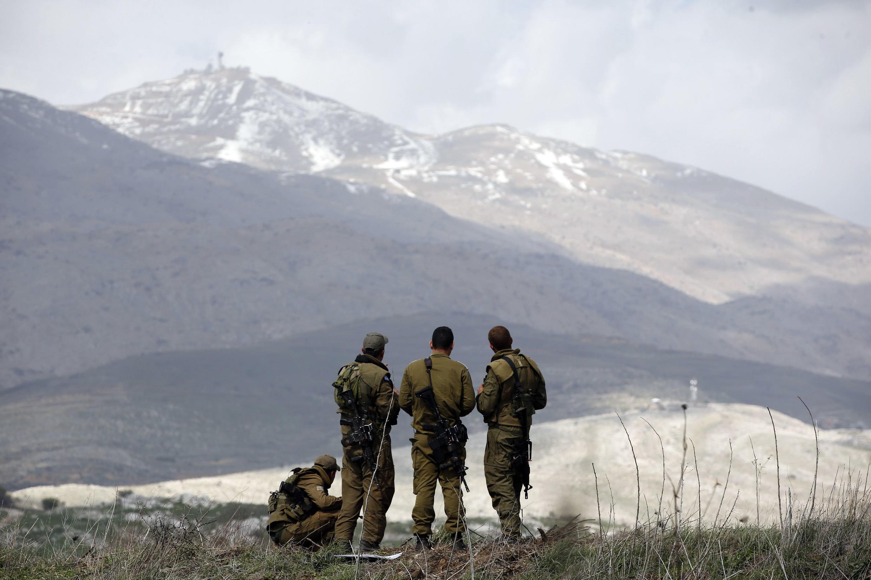 Des soldats israéliens regardent en direction de la Syrie, à partir du plateau du Golan.