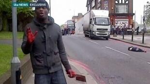 Um dos supostos assassinos de um militar em Londres com uma faca ensanguentada na mão diante das câmeras de  ITV News nesta quarta-feira, 22 de maio de 2013.