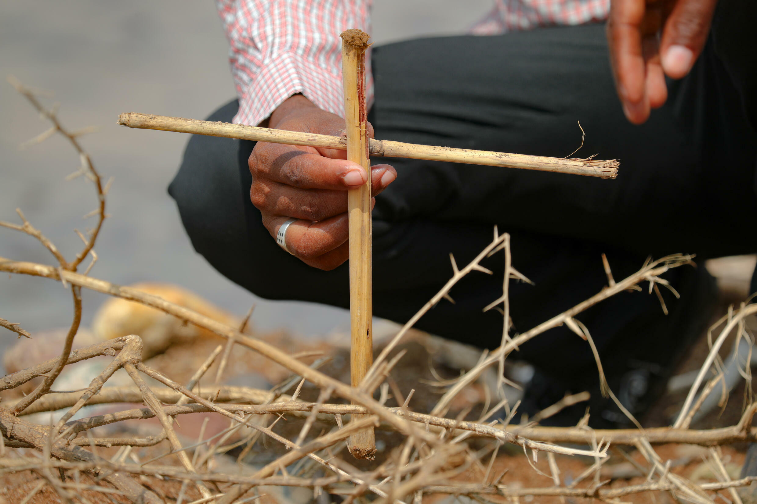 A Tigrayan refugee places a makeshift cross on the banks of the Setit River bordering Ethiopia