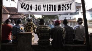 Pessoas sentadas junto a uma assembleia de voto, em Bissau. 24 de Novembro de 2019.