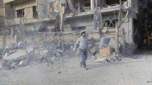 一名男子正走過大馬士革附近一個被敘利亞飛機轟炸後的廢墟  2012 年12月3日達利亞市