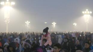 圖為天安門廣場上元旦日聚集民眾冒霾觀看升旗
