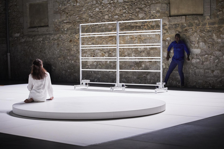 Nancy Huston seated, in contemplative mode with dancer, choreographer Salia Sanou in 'Multiple-s' in the Cour Minérale at the Avignon Festival