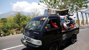 Des habitants de Bali fuient leur maison à bord d'une camionnette, alors que le volcan Agung (arrière-plan) commence à dégager de la fumée, le 29 septembre 2017.