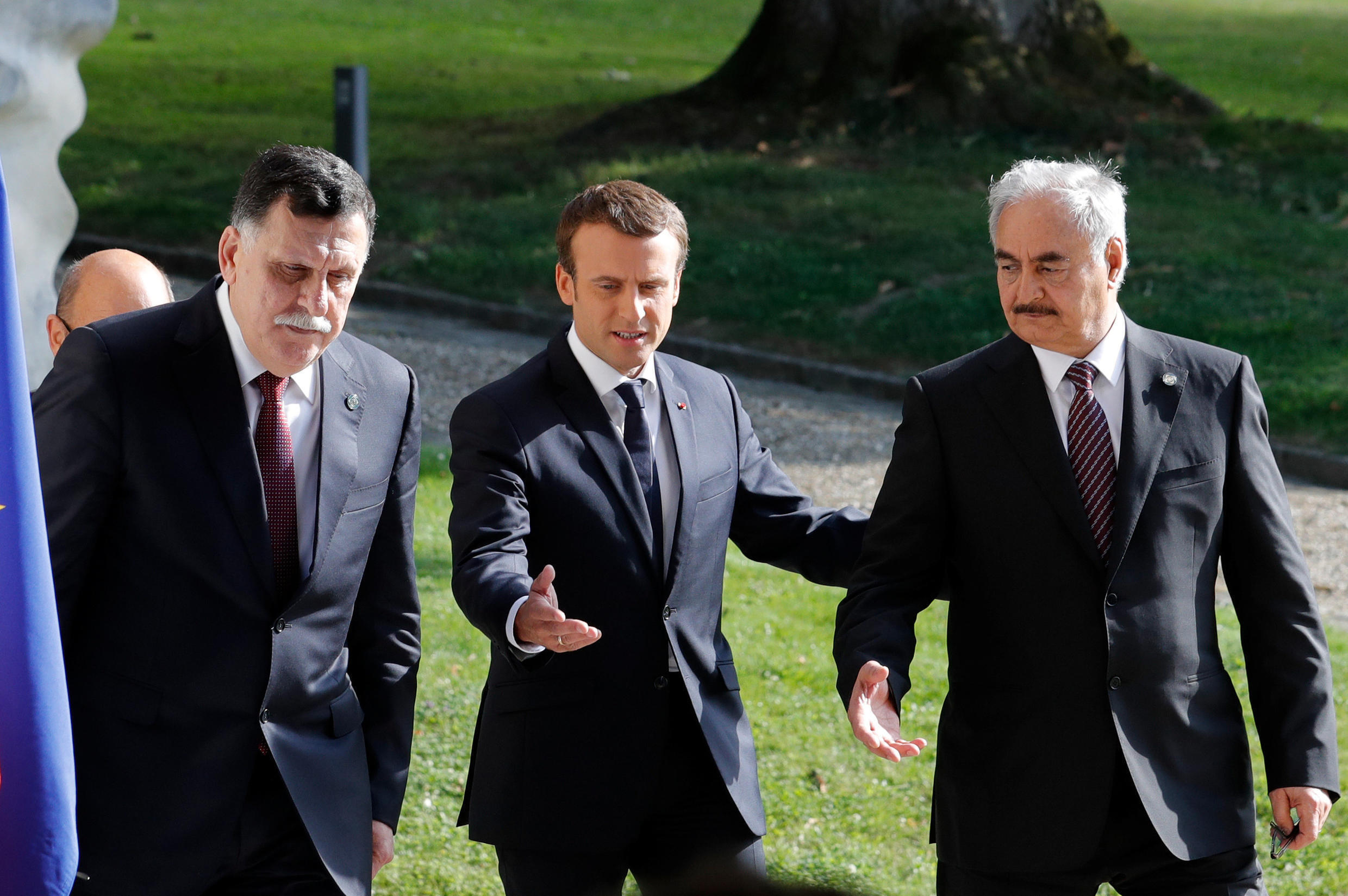 General Khalifa Haftar, commander in the Libyan National Army (R) and Libyan Prime Minister Fayez al-Sarraj (L) with French President Emmanuel Macron (M) after peace talks in La Celle-Saint-Cloud near Paris, on 25 July 2017.