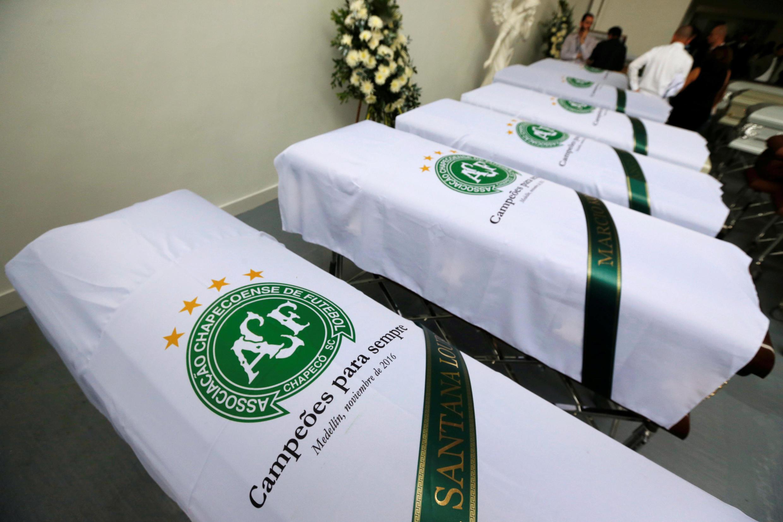 Cobertos com bandeira do Chapecoense, caixões com corpos das vítimas da catástrofe esperam traslado para o Brasil.
