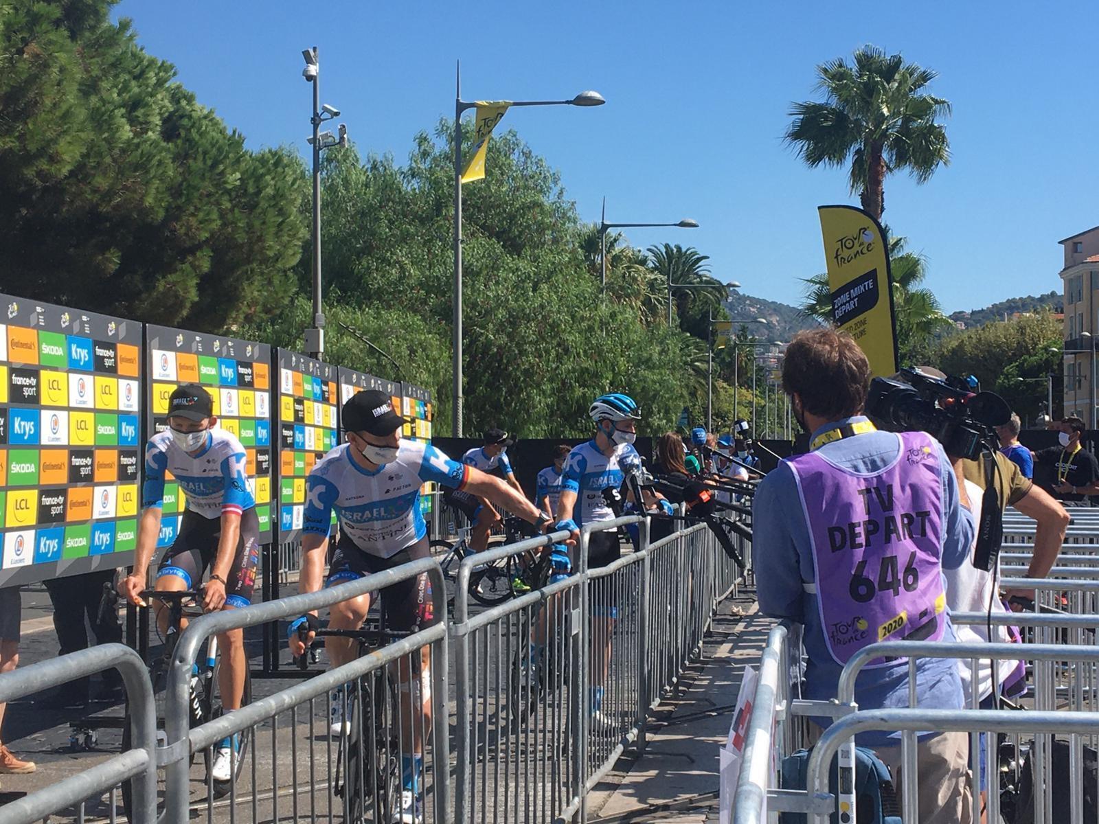Zona de prensa en la salida de cada etapa. Los medios y los ciclistas están separados por una barrera para mantener la distancia física.