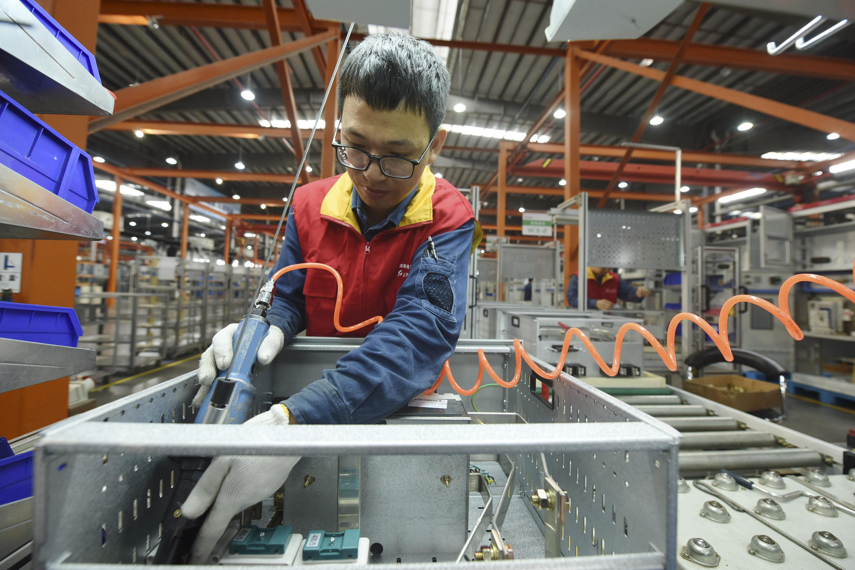 Công nhân lắp ráp thiết bị điện tại một chi nhánh của công ti phân phối điện Hàng Châu (Hangzhou), tỉnh Chiết Giang (Zhejiang), Trung Quốc. Ảnh chụp ngày 19/10/2020.