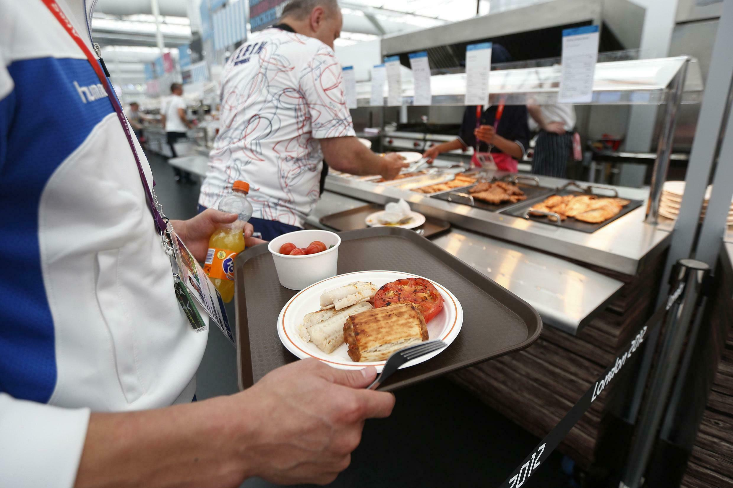 An athlete waits to be served in the dining hall inside the Olympic Games Village in Stratford
