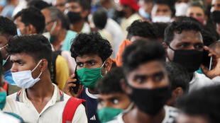 Plenty of masks, but not much social distance. Migrant workers waiting to be tested for coronavirus.