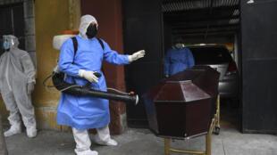 Un oficial de policía que lleva un traje de protección desinfecta el ataúd de una víctima de covid-19, en Ciudad de Guatemala el 29 de junio de 2020 Guatemala is approaching the 17,000 COVID-19 infections, while 727 people have died so far in the country.