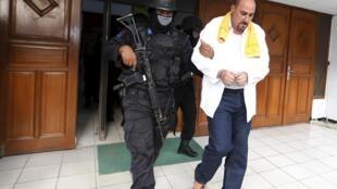 Серж Атлауи в сопровождении полицейского после заседания суда, 1 апреля 2015 г.