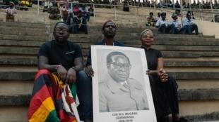 Un Zimbabwéen arbore le portrait de l'ancien président Robert Mugabe lors de l'homamge national qui lui est consacré, le 14 septembre 2019.