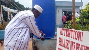 Un habitant de Conakry se lave les mains le 12 septembre 2014, l'une des mesures de prévention contre l'épidémie d'Ebola. Tout près de la fontaine publique, un panneau de sensibilisation.