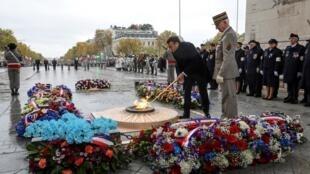 Tổng thống Macron châm lửa ở đài tưởng niệm chiến sĩ vô danh tại Khải Hoàn Môn trong lễ kỷ niệm 'Đình Chiến' 1918, Paris, ngày 11/11/2019.