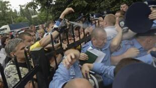 Des habitants en colère s'en prennent aux policiers et tentent de prendre d'assaut le poste de police local à Kiev, en Ukraine, le 12 juillet 2013.