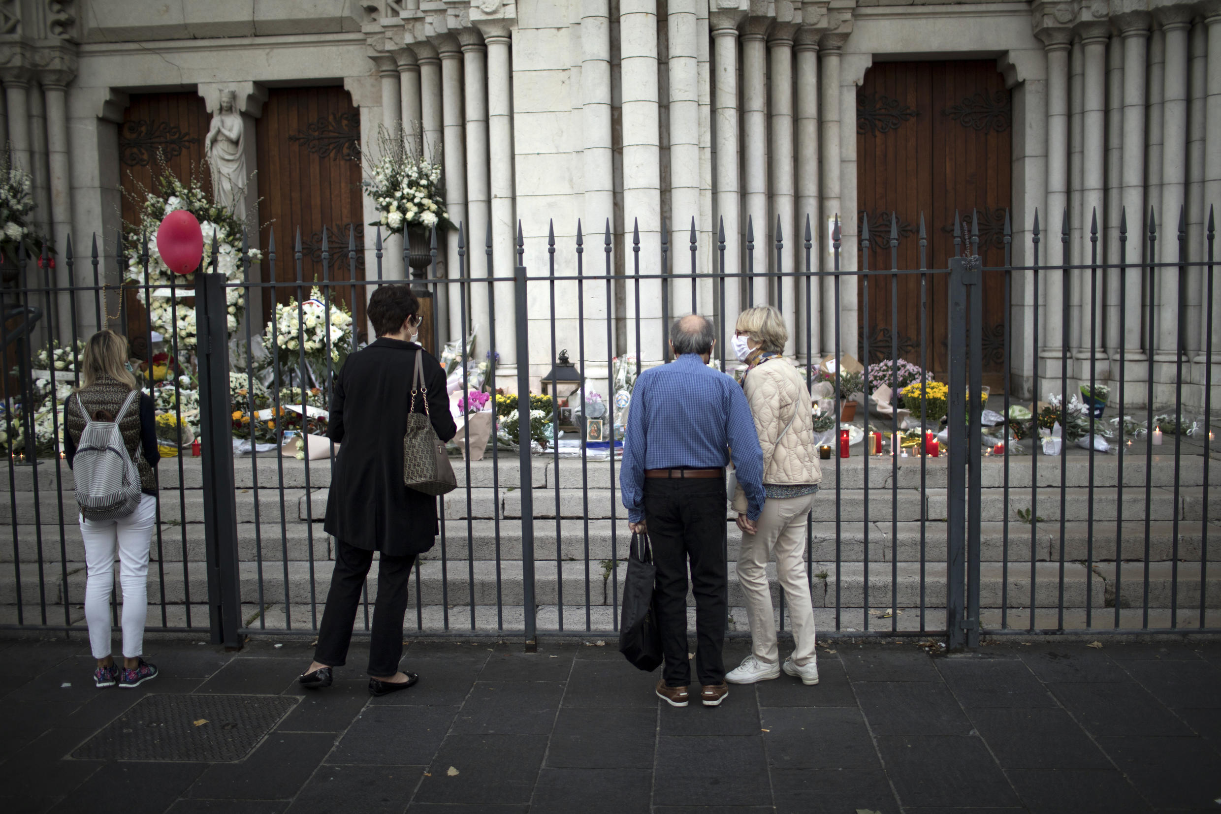 People pay respect to the victims in front of the Notre Dame church in Nice, France, Friday, Oct. 30, 2020. A new suspect is in custody in the investigation into a gruesome attack by a Tunisian man who killed three people in a French church. France heightened its security alert amid religious and geopolitical tensions around cartoons mocking the Muslim prophet.