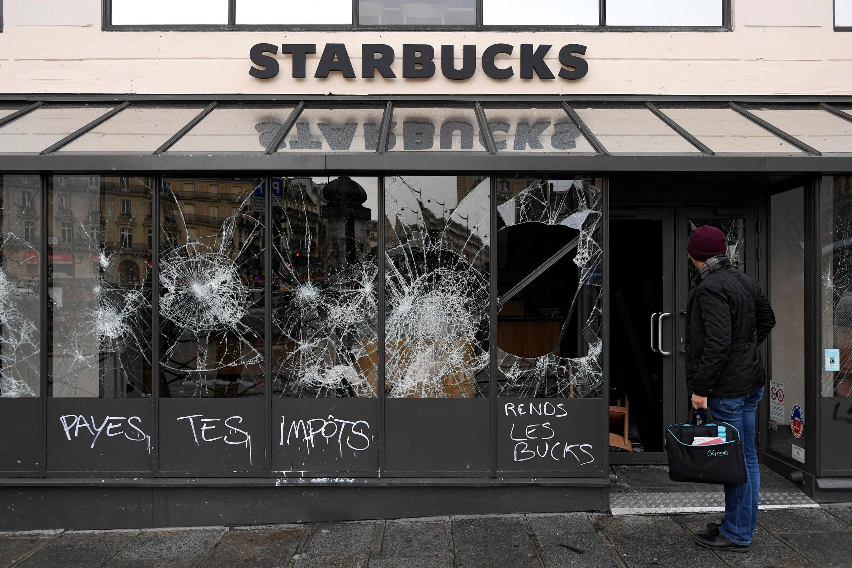 """Pichação e vitrines quebradas num café Starbucks no dia seguinte aos protestos dos """"coletes amarelos"""", em Paris."""