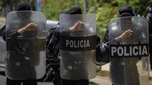 Riot police stand guard outside the house of presidential hopeful Cristiana Chamorro in Managua on June 2, 2021