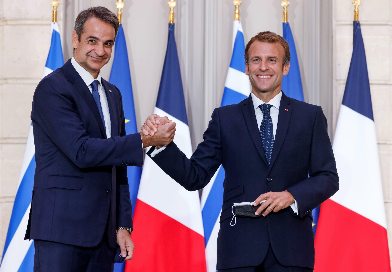 Kyriakos Mitsotakis (izq) y Emmanuel Macron se estrechan la mano tras la ceremonia de firma del acuerdo de defensa por el que Francia vende tres fragatas a Grecia, el 28 de septiembre de 2021 en el palacio presidencial del Elíseo, en París
