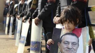 Menina egípcia segura cartaz com a imagem do ex-ditador Hosni Mubarak, em frente ao tribunal onde ele é julgado nesta terça-feira, no Cairo.