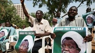 In this file photo, protesters hold banners calling for the release of Sheikh Ibrahim Zakzaky, the leader of the Islamic Movement of Nigeria (IMN), in Abuja, Nigeria.