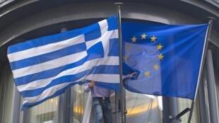 Funcionário ajeita as bandeiras da Grécia e da Europa na janela da embaixada grega, em Bruxelas, em 19 de fevereiro de 2015.