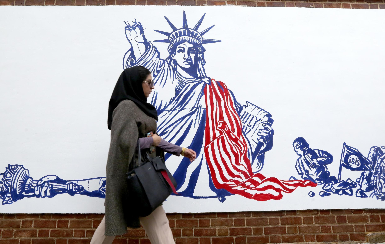 Une Iranienne passe devant l'une des fresques antiaméricaines inaugurées devant l'ancienne ambassade américaine de Téhéran, le 2 novembre 2019.