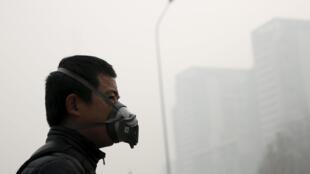 Um homem usando uma máscara num dia bastante poluído em Pequim.