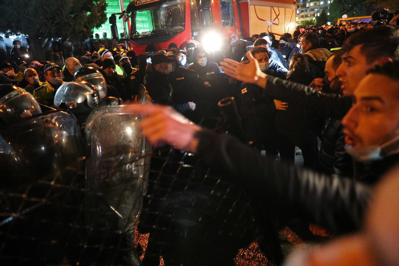 Демонстранты выкрикивают лозунги, пока ОМОН стоит на страже во время митинга оппозиции у здания ЦИК. Тбилиси. 08.11.2020.