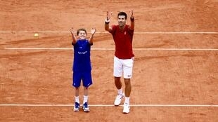 Novak Djokovic celebrates a victory with a ball boy at Roland Garros 2016