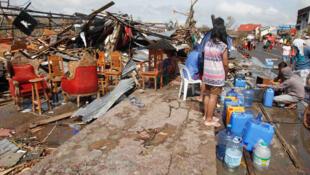 Sobreviventes do tufão Haiyan fazem fila para obter água potável na cidade destruída de Tacloban.